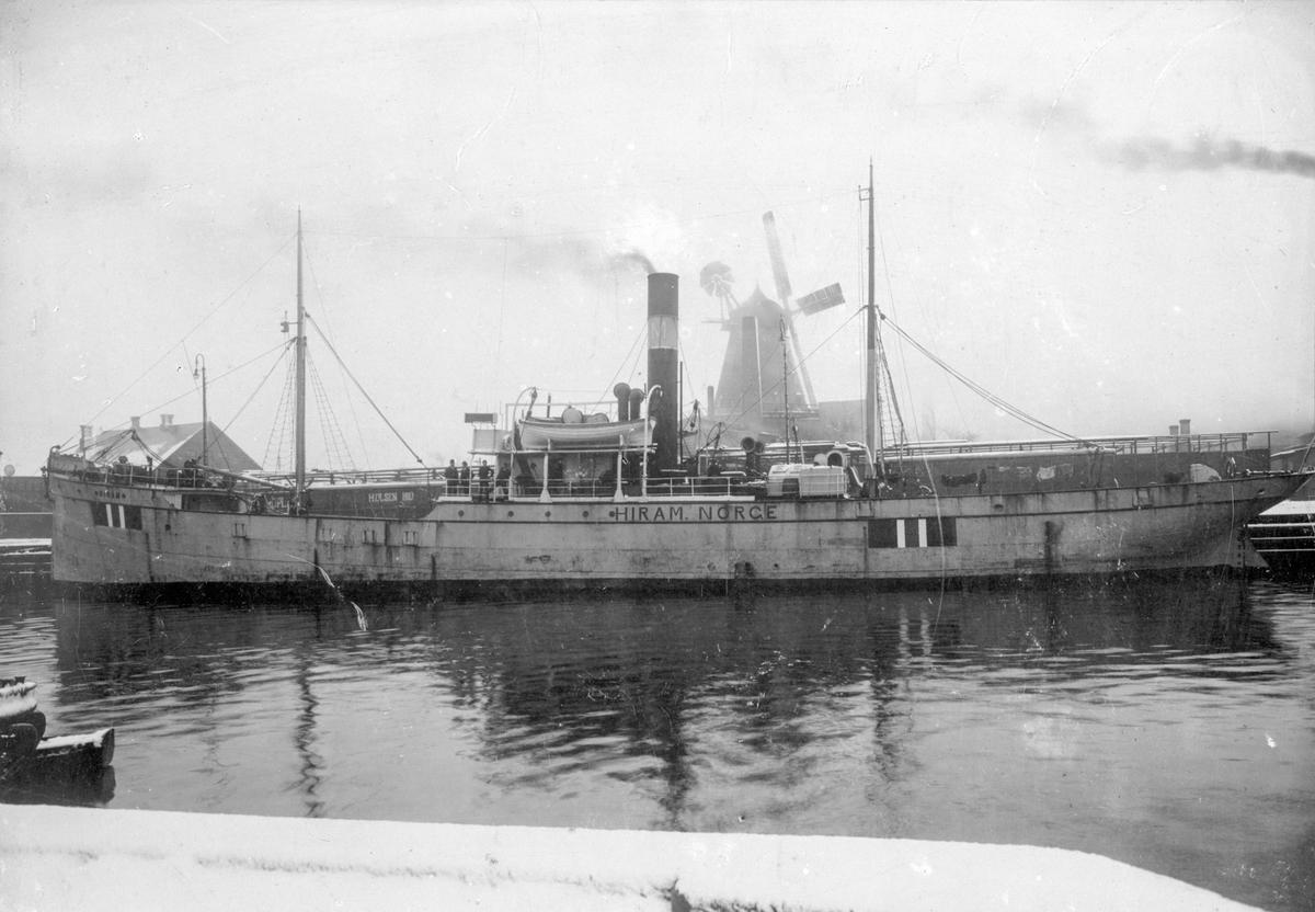 """Damskipet D/S """"Hiram"""" ved havn i utenlandsk by. I bakgrunnen står en stor vindmølle. Det er et tynt lag med nysnø på land og klesvask henger til tørk på dekk."""