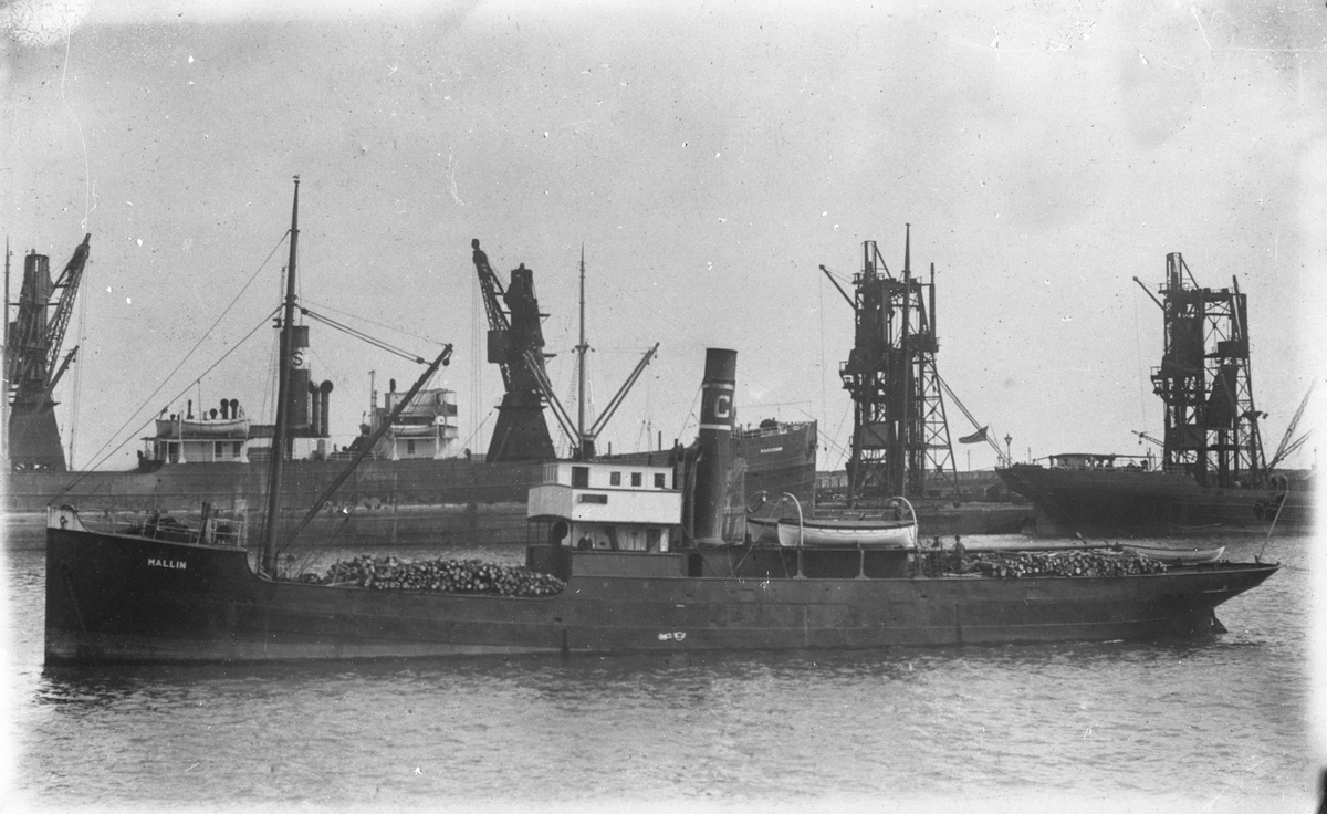 """Damskipet D/S """"Mallin"""" med trelast ved et industristed. I bakgrunnen er fire store kraner."""