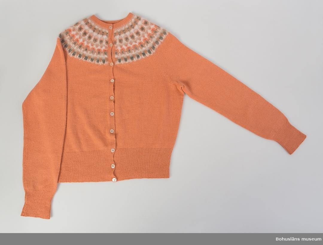 """Kofta i gulröd /""""aprikos"""" färg med mönster i färgnyanser i vitt, beige, grön och orange. Mönstret """"Canna"""" av Annika Malmström-Bladini. Etikettmärkt """"Bohus Stickning"""", raglanärm, knäppt framtill med tio knappar."""