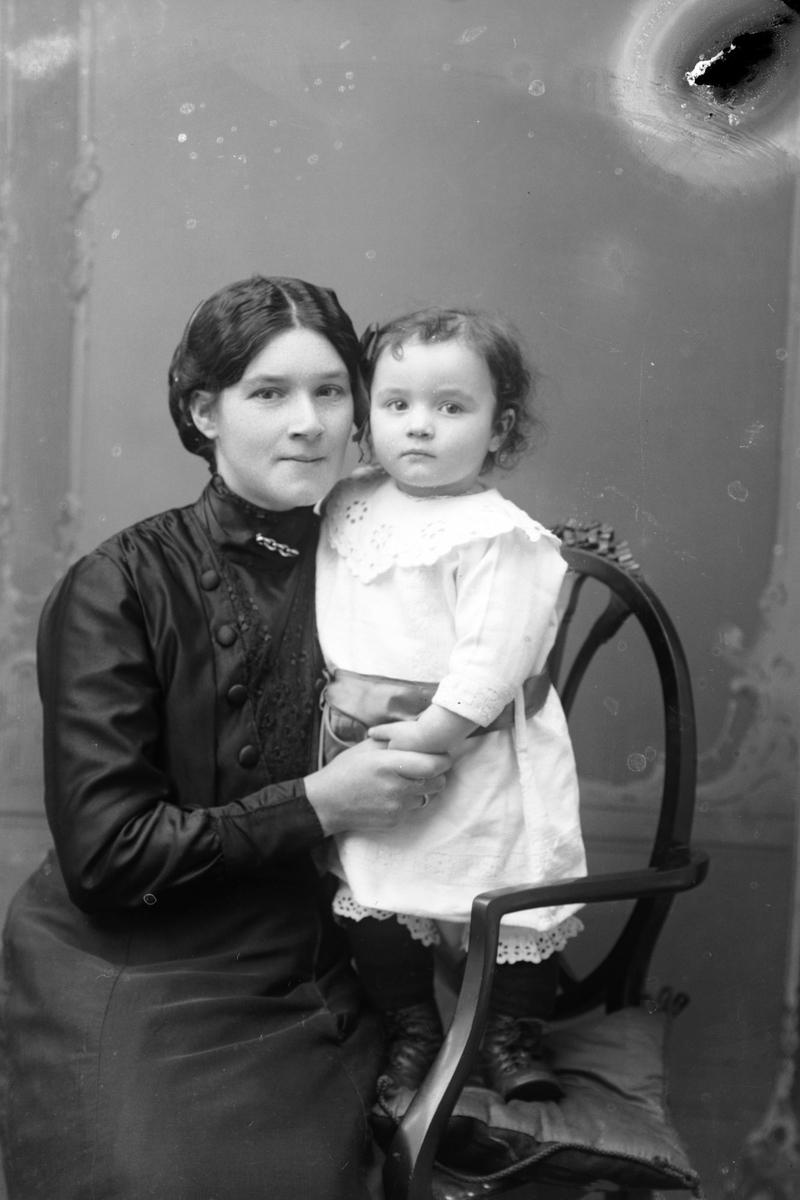 Studioportrett av en kvinne med et barn i armene.