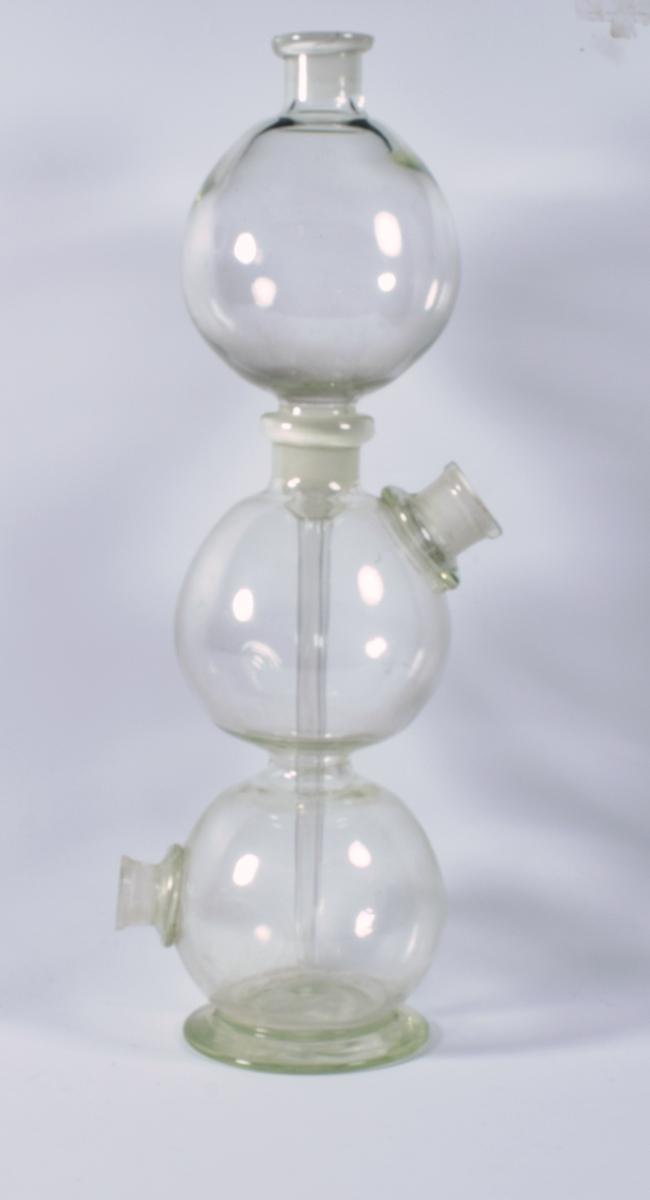 Apotekinstrument i klart glass. Gjenstanden består av tre glasskuler som er satt sammen oppå hverandre. Den nederste kula går ut i en flat sokkel. Denne kula har en åpning/tut på den ene siden, som står horisontalt ut fra kula. Den nederste kula henger sammen med den miderste kula. Denne kula har en åpning/tut skrått oppover nesten på toppen av kula, på motsatt side av åpningen/tuten på den nederste kula. Den miderste kula har på toppen nok en åpning, og her er den øverste kula plassert. Den øverste kula er ikke festet sammen i de to andre, den bare hviler på de to gjennom åpningen på toppen i den miderste kula. Den øverste kula her en tut/åpning øverst. Nederst går kula sammen til et smalt glassrør som går inn i den miderste kula og videre ned i den nederste kula. Dette er et Kipps luftutviklingsapparat og brukes til fremstilling av gasser som for eksempel karbondioksid og dihydrogensulfid.