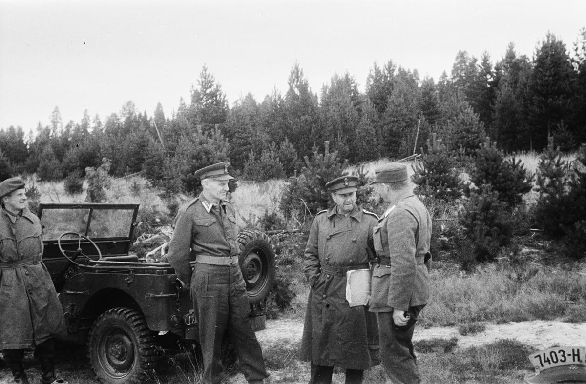 Militærøvelse. 4 menn. Parkert jeep.