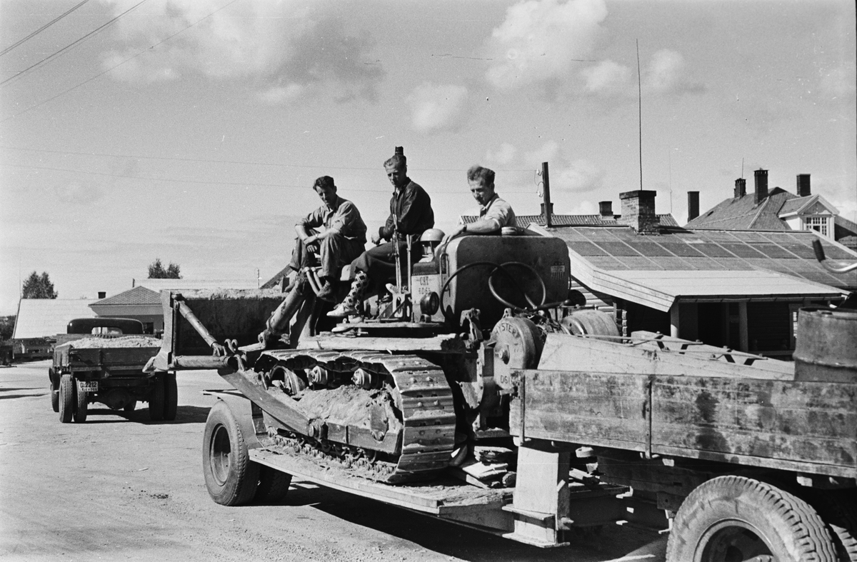 Bulldozer på lastebilhenger. Tre menn. Leiret, Elverum.