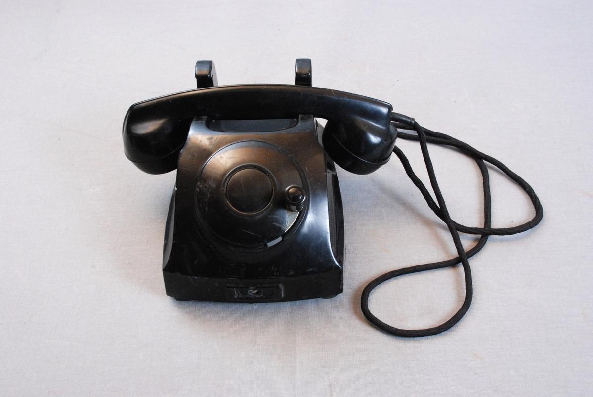 Telefonapparat med telefonrør på gaffel med kontakter/brytere. Ledning fra telelfonrør til apparat. Apparatet har firkantet grunnform, skrånendeoppover på fremsiden med plass for rund nummerskive. Denne plassen er dekket av en rund plate med sveiv.