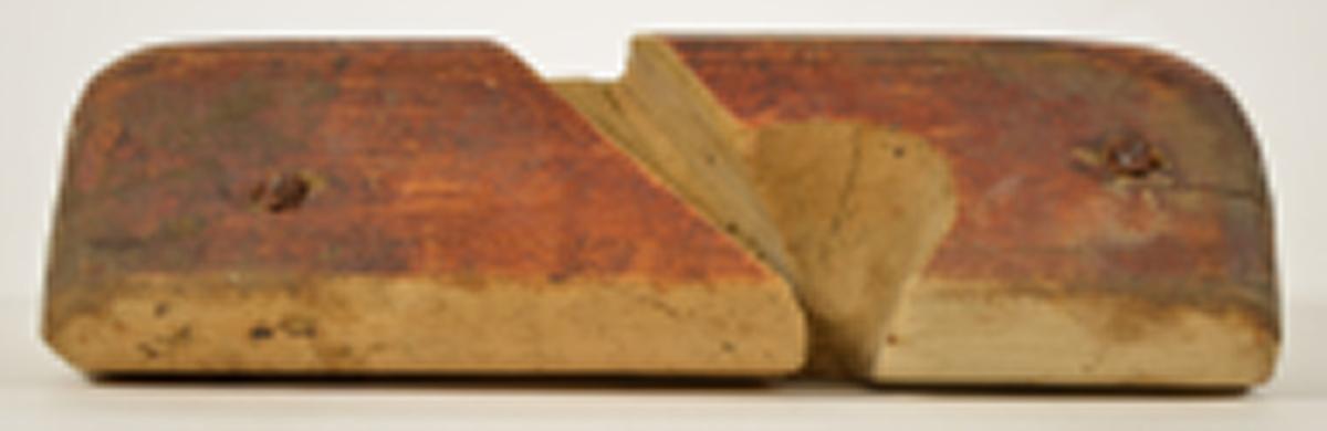 Rektangulær, rødmalt stokk med sponhus, avrundede topphjørner,  og konveks (buet) såle. To jernskruer gjennomgående på hver side.