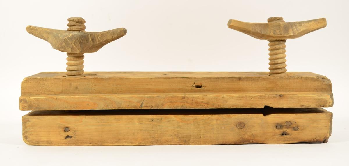 Rektangulær presse med håndsmidde skrutvinger og dreiede staver. På den ene siden er det laget to riller på pressens inside.