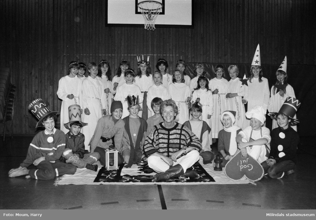 """Luciafirande på Hallenskolan i Kållered, år 1984. """"Hela luciaensemblen med sin omtyckta musiklärare Margarete Jonsson.""""  För mer information om bilden se under tilläggsinformation."""