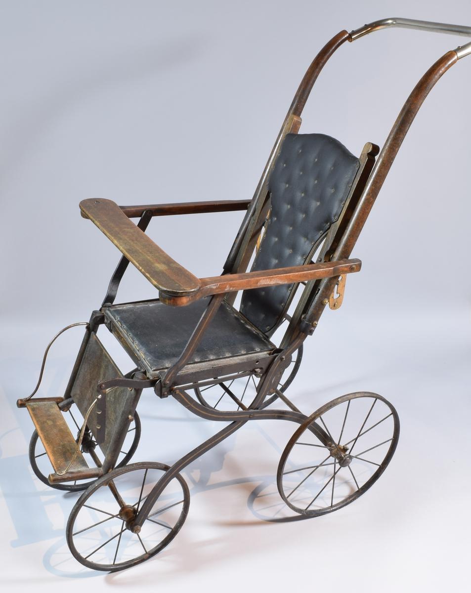 Barnevog/trillevogn tre og metall. Vogna har en ramme i metall og hjul i metall. Rundt setet og på fotstøtten er deler av vogna i tre. Ryggstøet er dekket av en tynn myk putedel trukket med en slags vokstrukket tekstil. Det samme gjelder for setet der en plate med pute trukket med vokstrukket tekstil er festa som en liten plate oppå treet i setet. Vogna har en treplanke tvers over foran som vil hindre barnet i å falle ut. Hjulene har smale gummiringer.