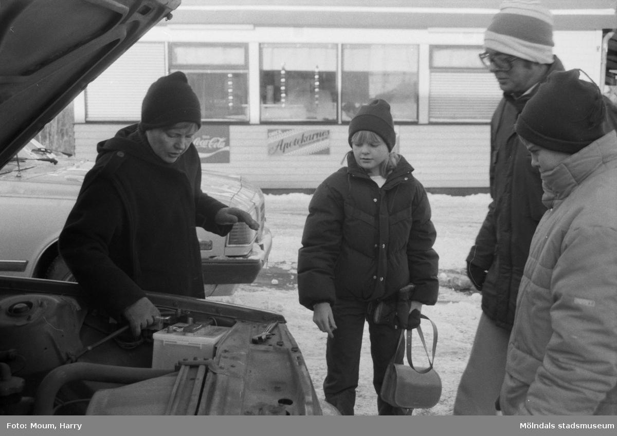 """""""Familjen Norén från Lindome hade just fått starthjälp av en granne och svängde upp framför Texaco och tog raka vägen in för att köpa nytt batteri, som med viss möda kom på plats. Därefter spann motorn igång utan mankemang."""" Lindome, år 1985.  För mer information om bilden se under tilläggsinformation."""
