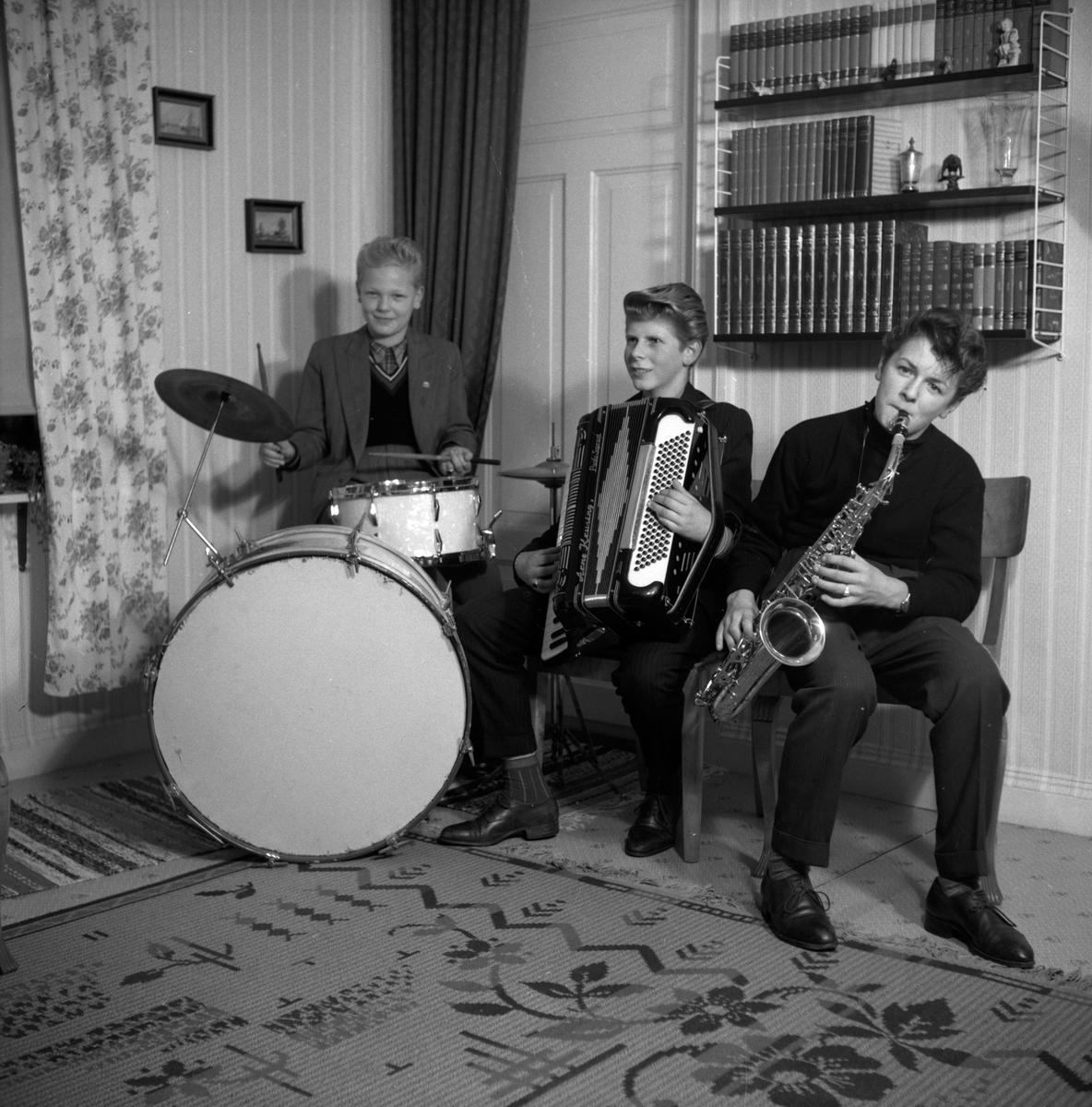 Hos Dahlgren, Tullportsgatan 9 i Jönköping. Musicerande pojkar med trummor, dragspel och saxofon. På väggen sitter den moderna stringhyllan.