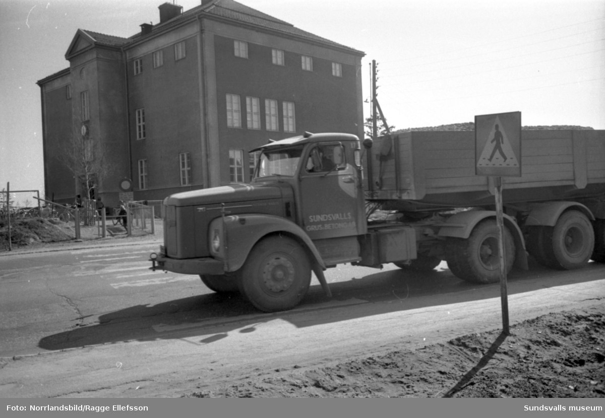 Grusbilar dundrar förbi Vapelnäs skola.