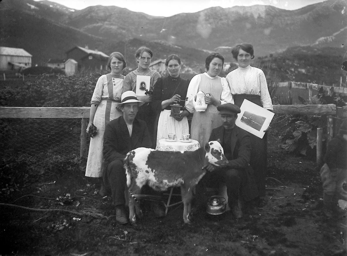 6 personer og en kalv ute. Hus. Mann med hatt og 5 kvinner, ca. 20 år. Mannen sitter ved et bord. Kvinnene står bak, kalven foran. Hus/fjell i bakgrunnen. 2 kvinner med hvert sitt bilde, landskapsbilde - portrettbilde. Kopper på bordet. Kvinne med kaffekanne. Utebilde. Saura. Nygårdsjøen.