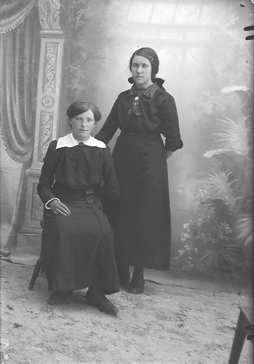 Portrett. To jenter i tenårene. To konfirmanter. Gildeskål. 1915. Jenta som står er sannsynligvis samme jente som på NM 8243:1413.