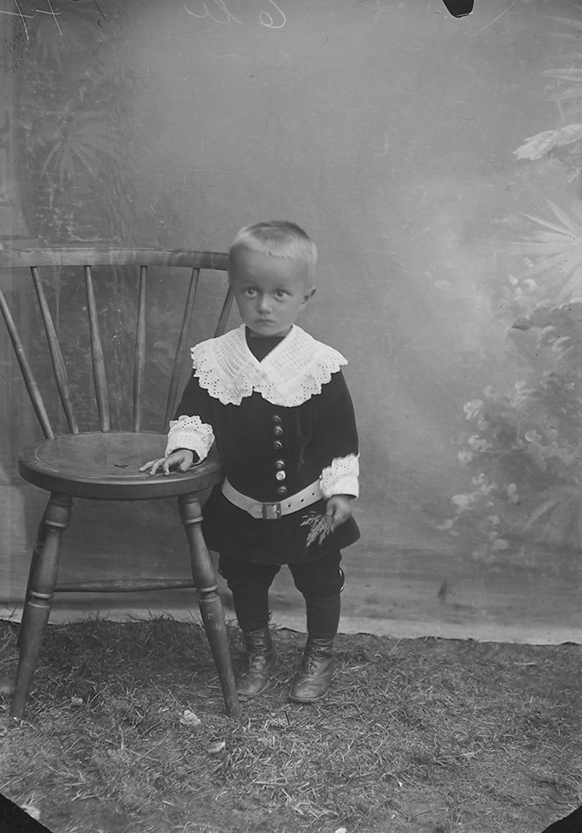 Portrett. Gutt, ca. 4 år. Står ved en stol.Bildet er tatt i Sørfold.