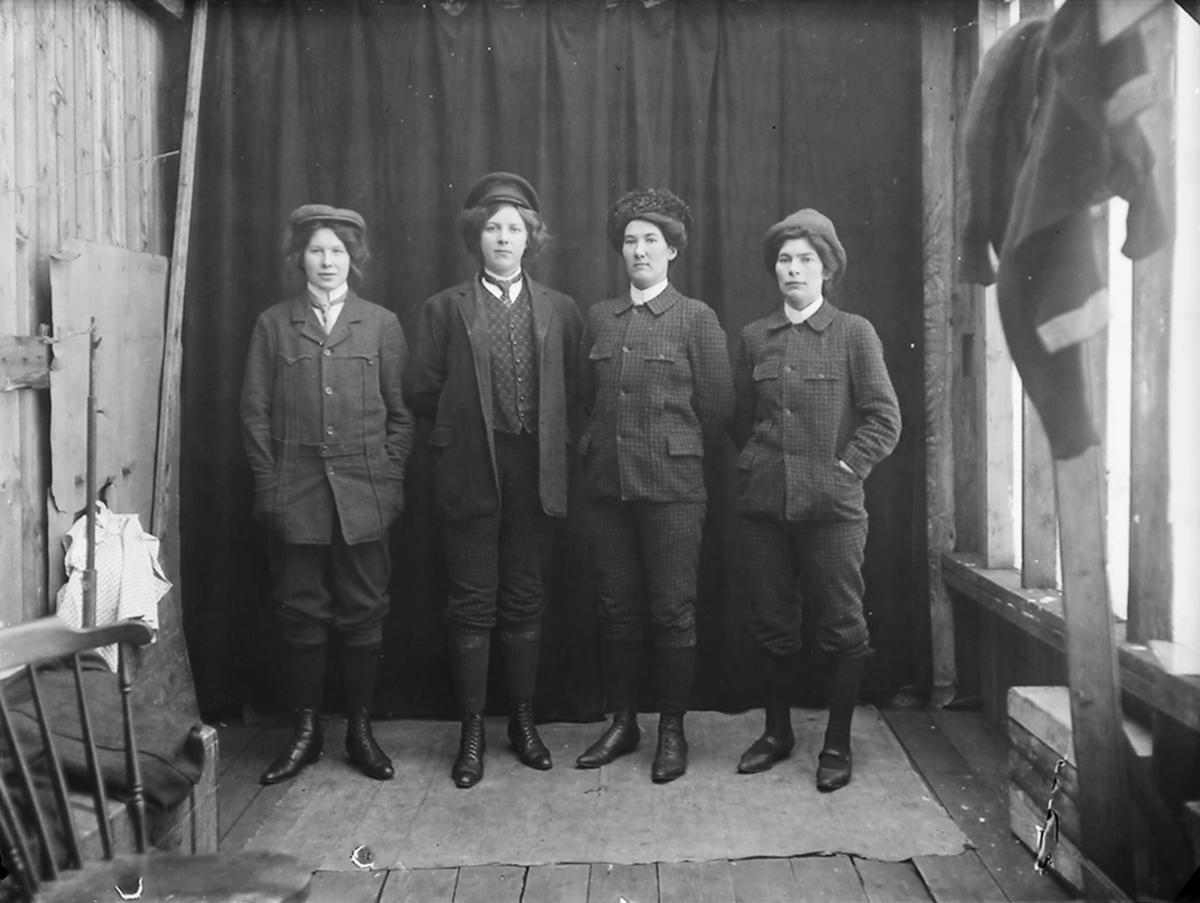 Gruppebilde. 4 jenter har kledt seg ut som menn. Nr. 3 fra venstre er Paula Josefine Pettersen, f. 1887. Nr 4 fra venstre er Magda Johansen, f. 1891.
