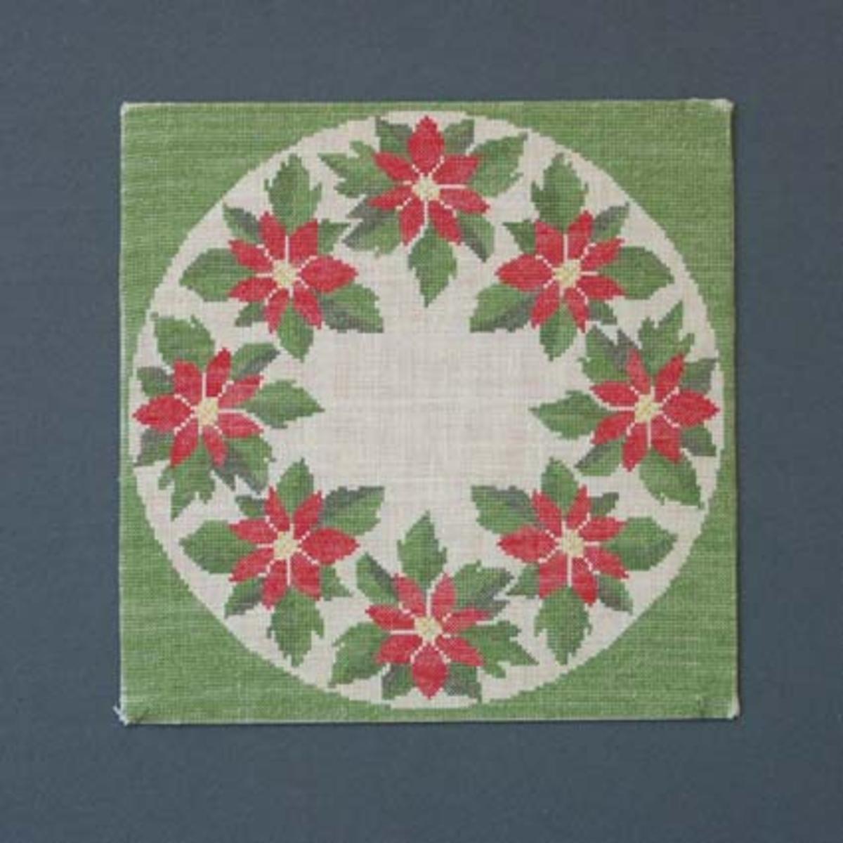Julbonad med korsstygnsbroderi på linneväv. Bonaden tillhör Runda serien som är en serie julbonader formgivna av Irma Kronlund, en bonad per år från 1971 till 1989.Pris material med mönster 175:-.