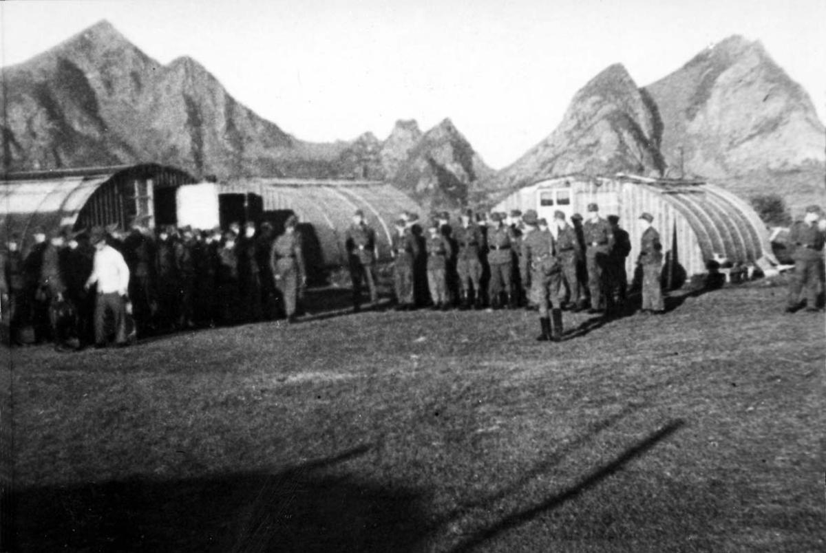 Militært anlegg, festningsområde. Gruppebilde, flere personer, menn i militæruniform ved noen bygninger