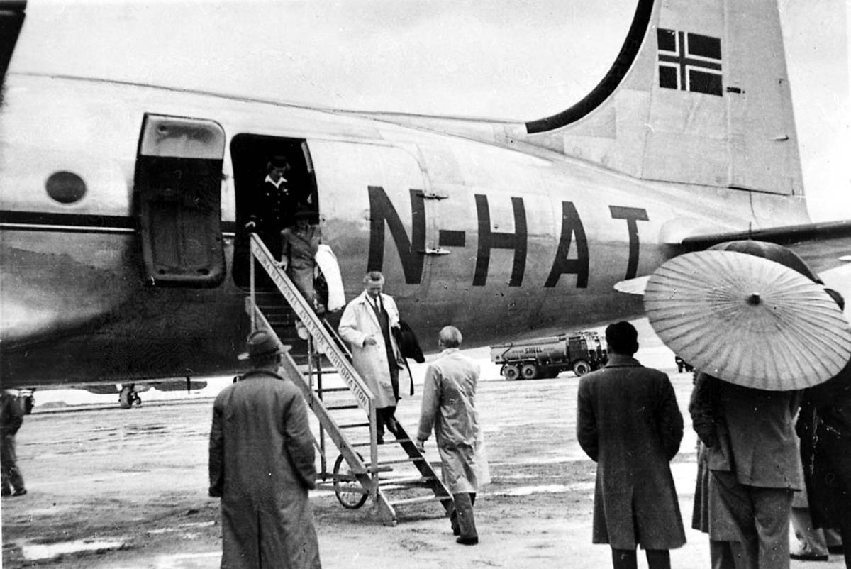 """Lufthavn. 1 fly på bakken, Douglas DC-4 C-54A, LN-HAT """"Norse Skyfarer"""" fra Braathens SAFE. Flere personer ved flyet, noen på vei ned landgangen."""