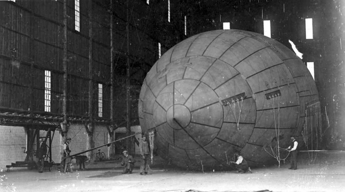 Luftskipshangar innvendig. Ett luftskip inne i hangaren og flere personer.