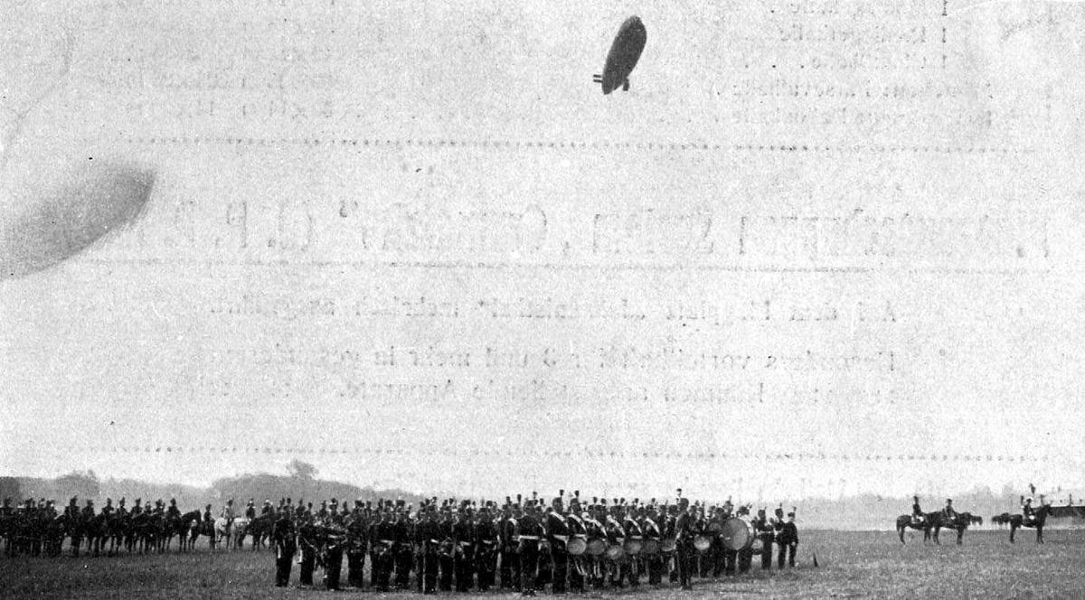 """Utklipp: Ett luftskip like over bakken, Astra-Torres I """"Vedette"""". Mange personer, militært personell, oppstilt på bakken under luftskipet. Noen av dem med musikkinstrumenter."""