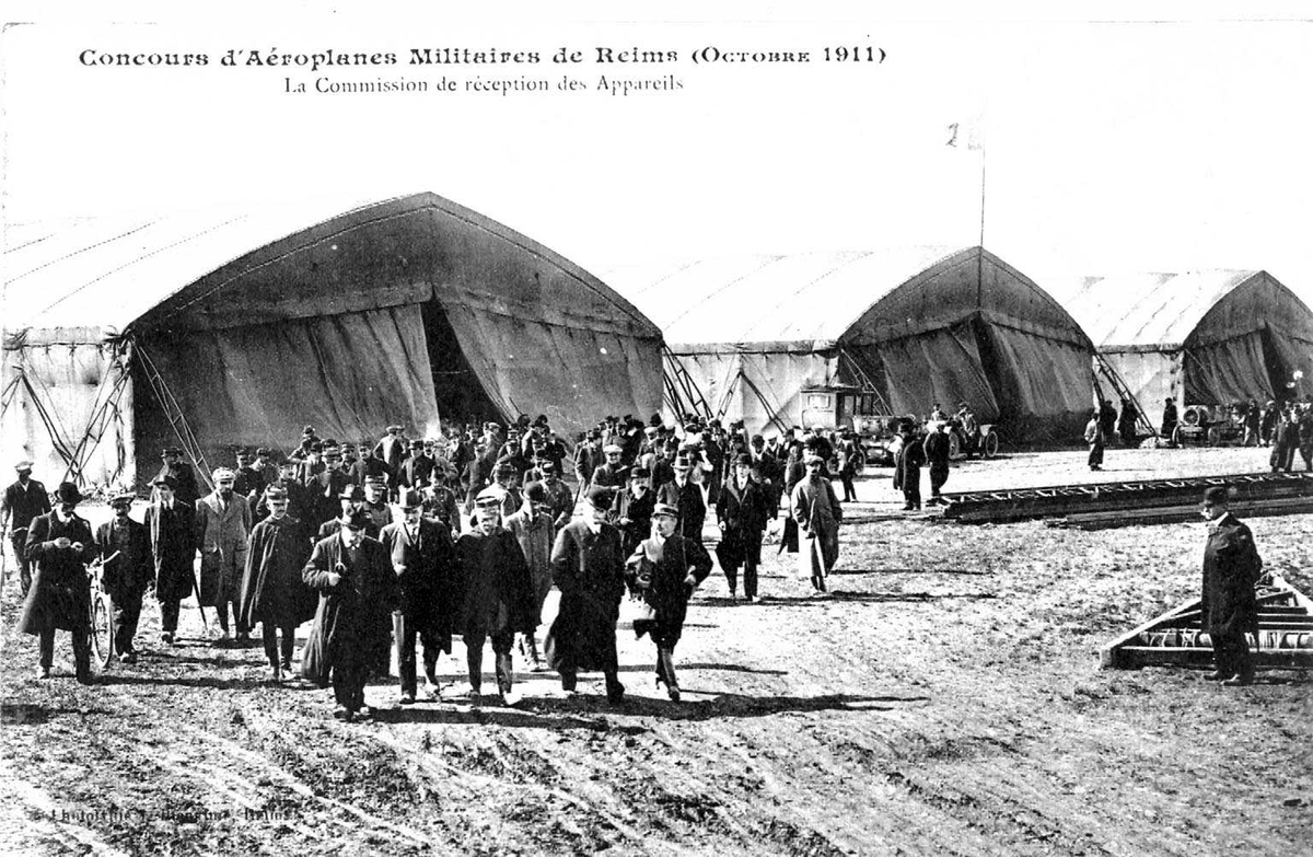 Utstilling.Åpen plass med mange personer. Telt (hangarer) i bakgrunnen.