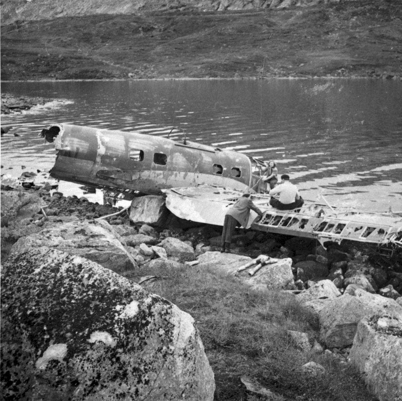 Ett flyvrak ved vannkanten, He 111H-3, 1H+DN. En person, mann, ved flyvraket.