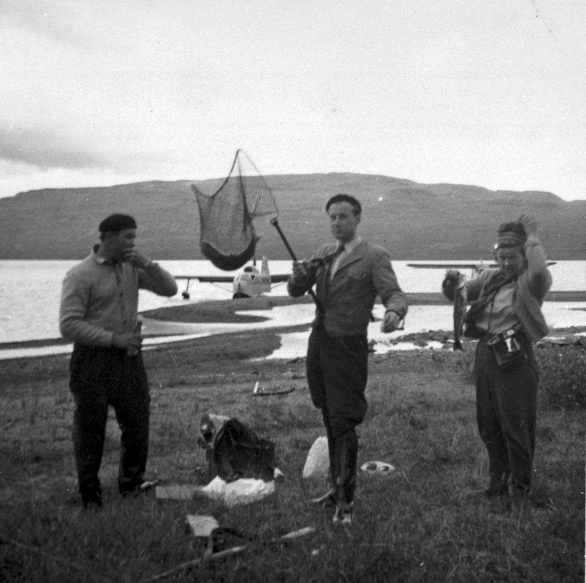 Tre personer med fiskeutstyr og fisk/ørret. To fly i bakgrunnen