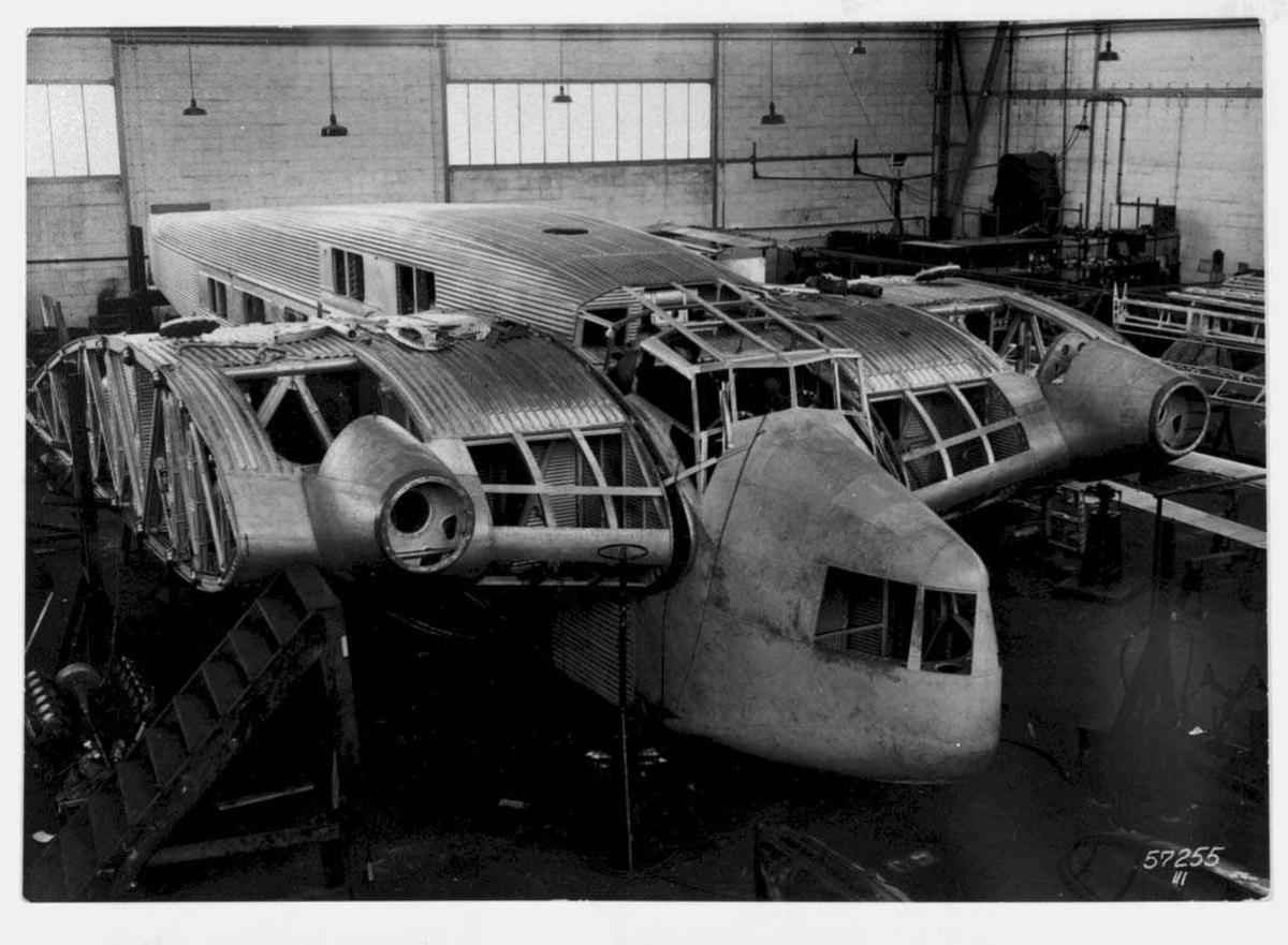 """Ett fly på bakken Junkers G 38b fra Luft-Hansa, inne i en hangar. Delvis """"demontert"""". Noem personer ved flyet"""