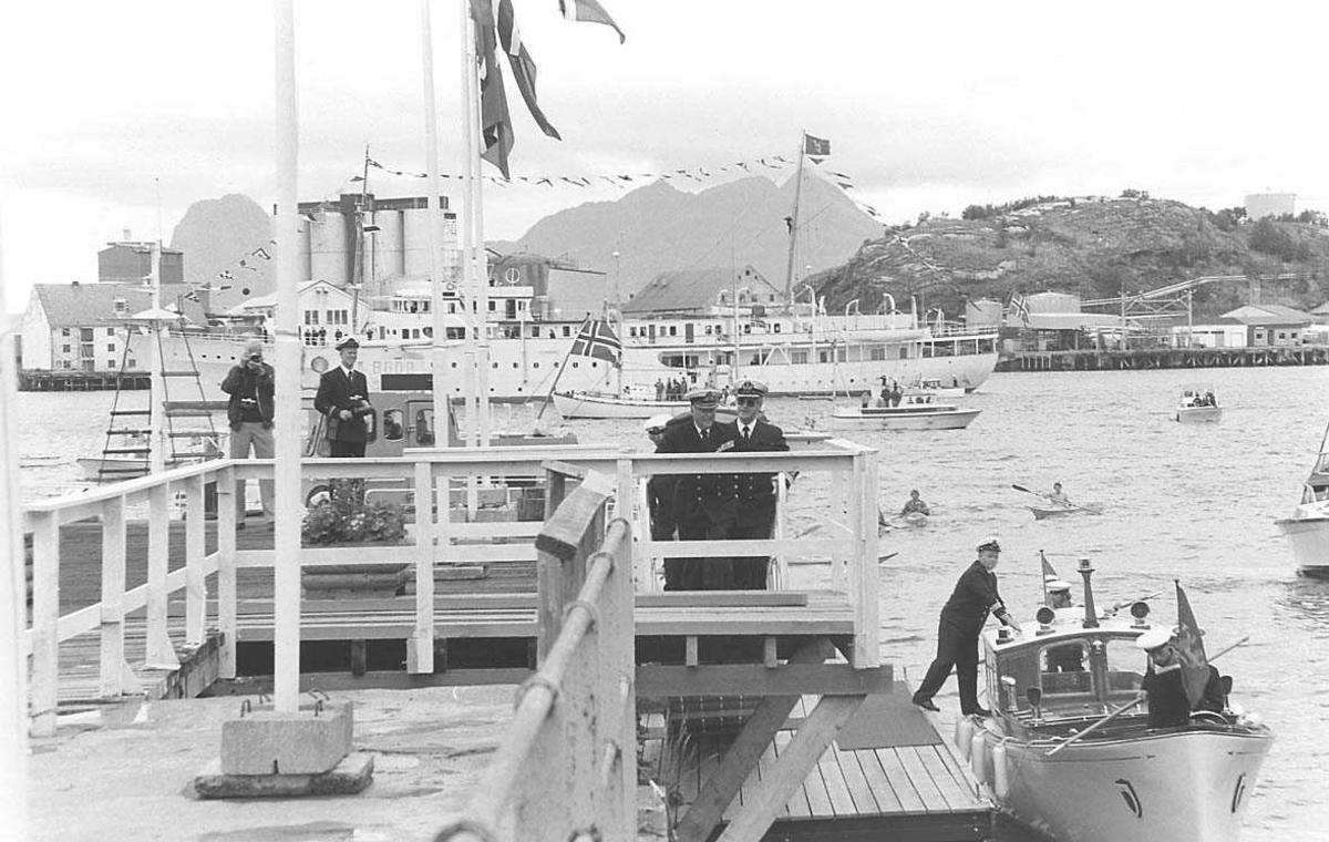 Personer som kommer i land fra en båt. Båter, bygninger, siloer og tankanlegg i bakgrunnen.