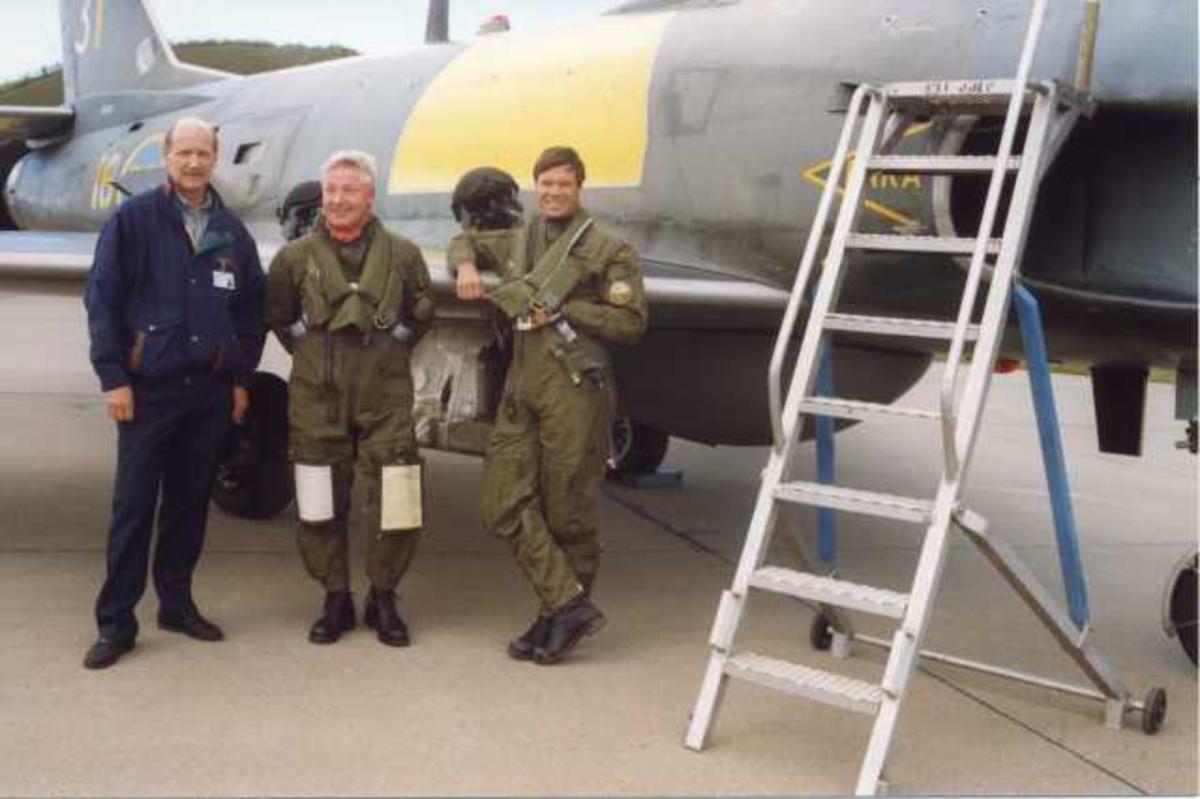 Lufthavn (flyplass). Ett fly på bakken, SAAB-32 Lansen, toseter. Tre personer, menn, i forgrunnen. To av dem i militæruniform, piloter - flygere.