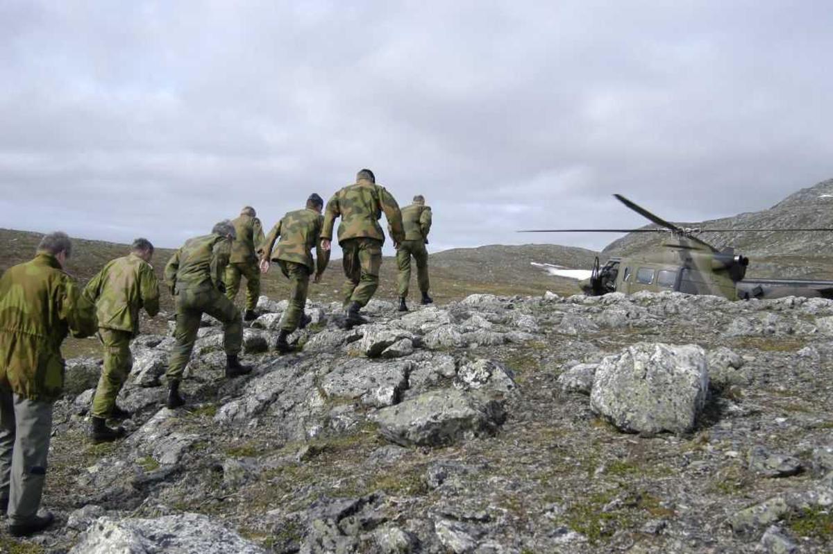 Høydedrag. Ett helikopter i lufta. Bell 412SP Arapaho 142 fra 339 Skv. på bakken. Noen personer, menn i militæruniform, på vei mot helikopteret.