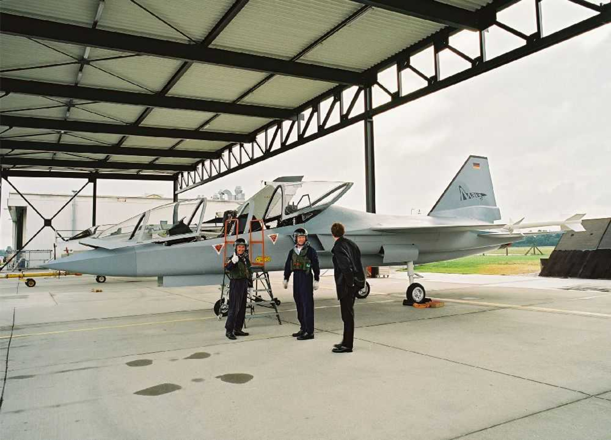 Ett fly på bakken, Mako jettrainer. Tre personer ved flyet. Flygere (pilot).
