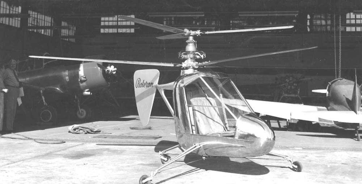 Ett helikopter på bakken, Roteron XM-1. Har to rotorer overnfor hverandre. Står foran en hangar med flere fly i.