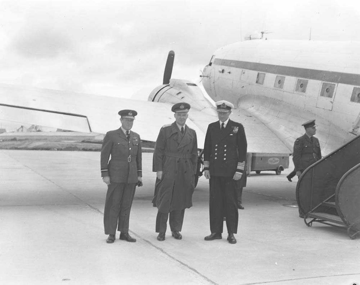 Lufthavn. Fire personer (militært personell) foran et fly