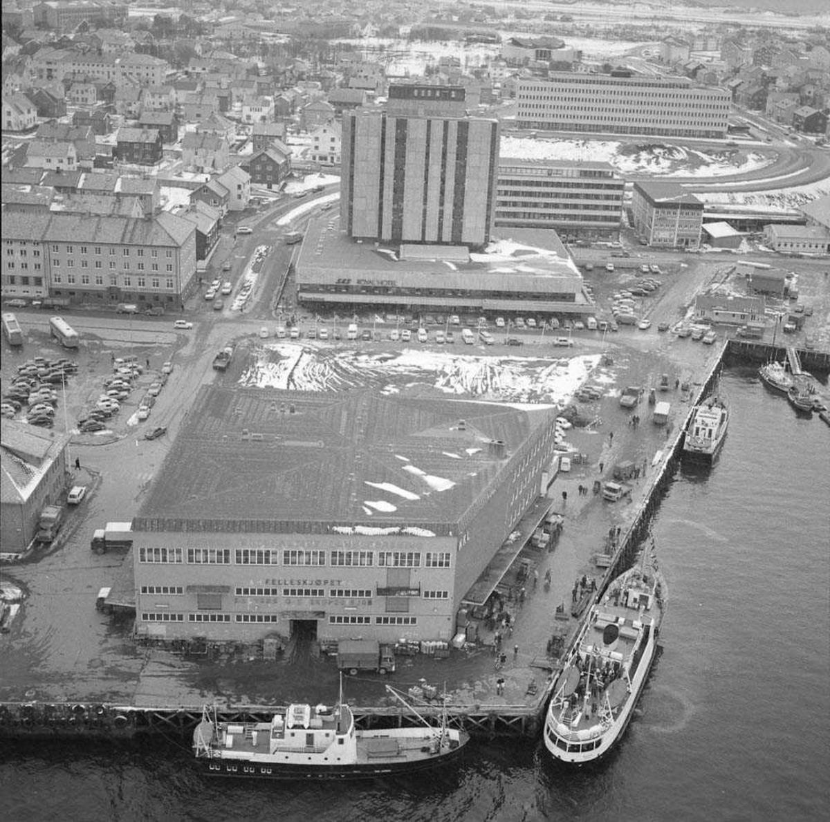 """Åpningen av Hotel SAS Royal i Bodø. Hotellet sees midt på bak i bildet. Det lange hvite bygget helt bak og til høyre er Nordland Fylkesbygg. Helt framme til høyre sees båten """"Salten""""."""