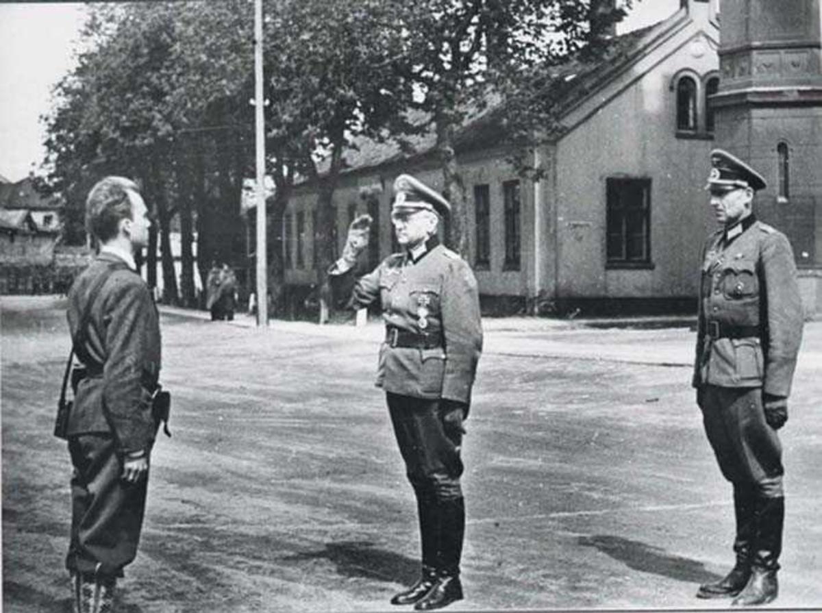 Tre personer, menn i militæruniform. To tyske offiserer. En soldat fra hjemmefronten. Bygning i bakgrunnen.
