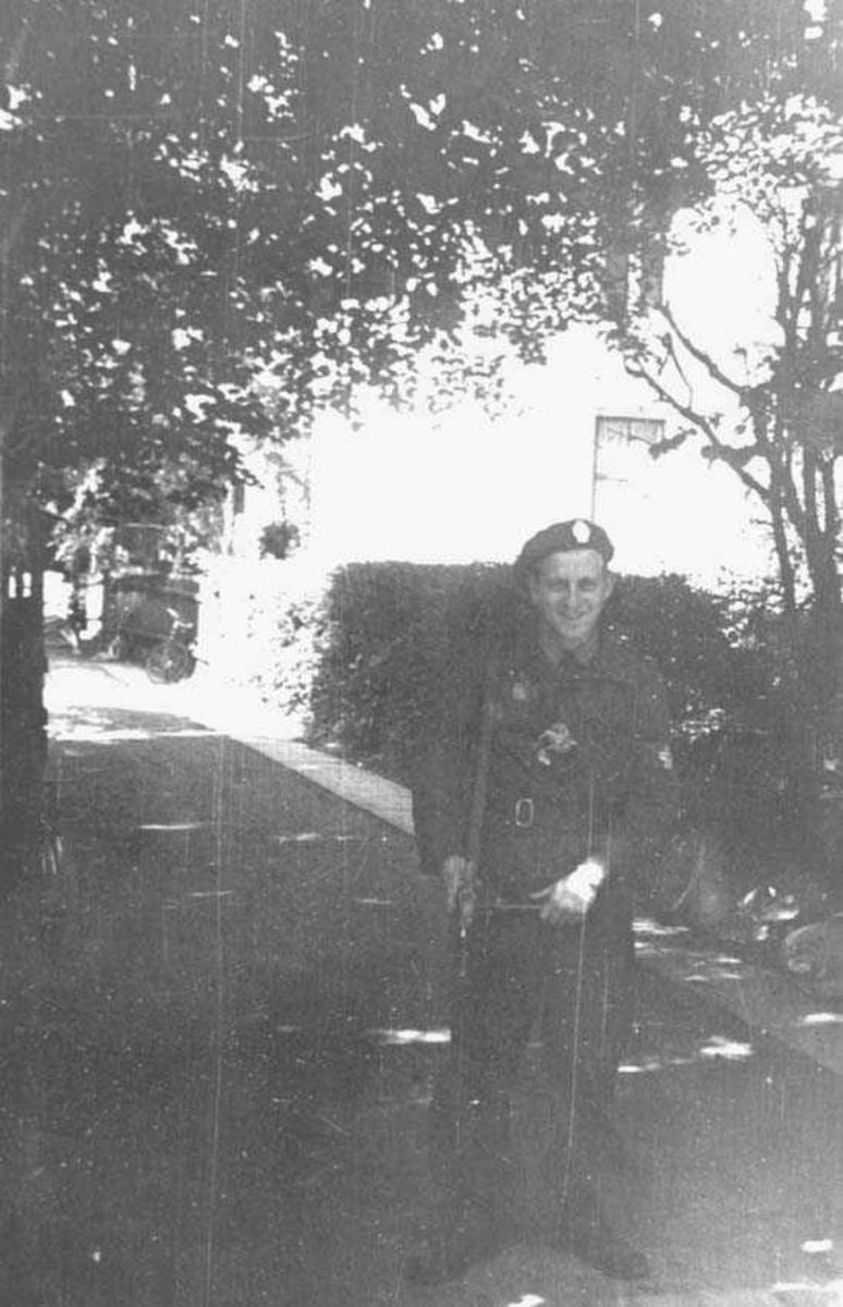 En person. Mann. Står i uniform og har et våpen over skulderen. Bygning i bakgrunnen.