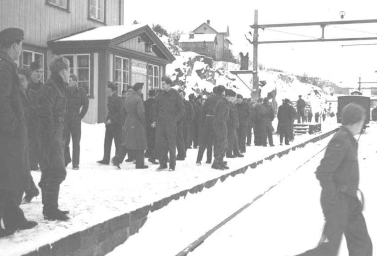Flere personer i militæruniform på en jernbaneplattform. Bygninger og jernbanevogn i bakgrunnen.