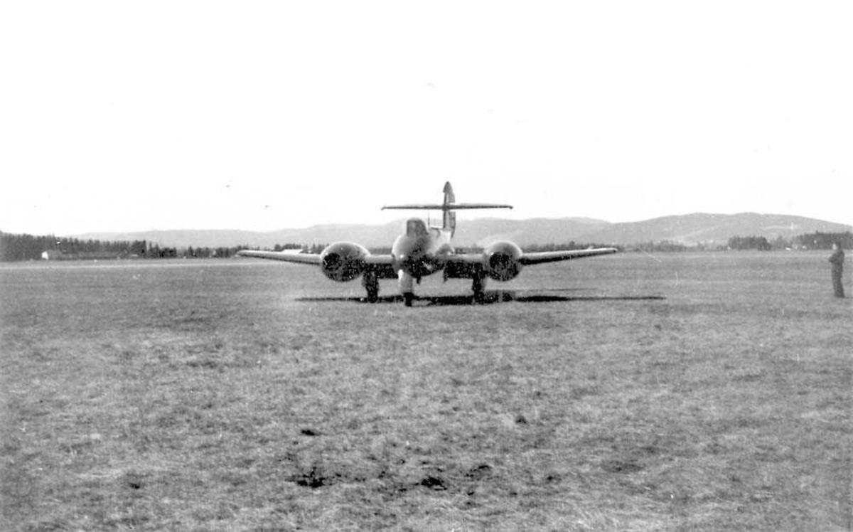 Ett fly på bakken, Gloster Meteor Mk IV. En person står til høyre for flyet. Fjell i bakgrunnen.