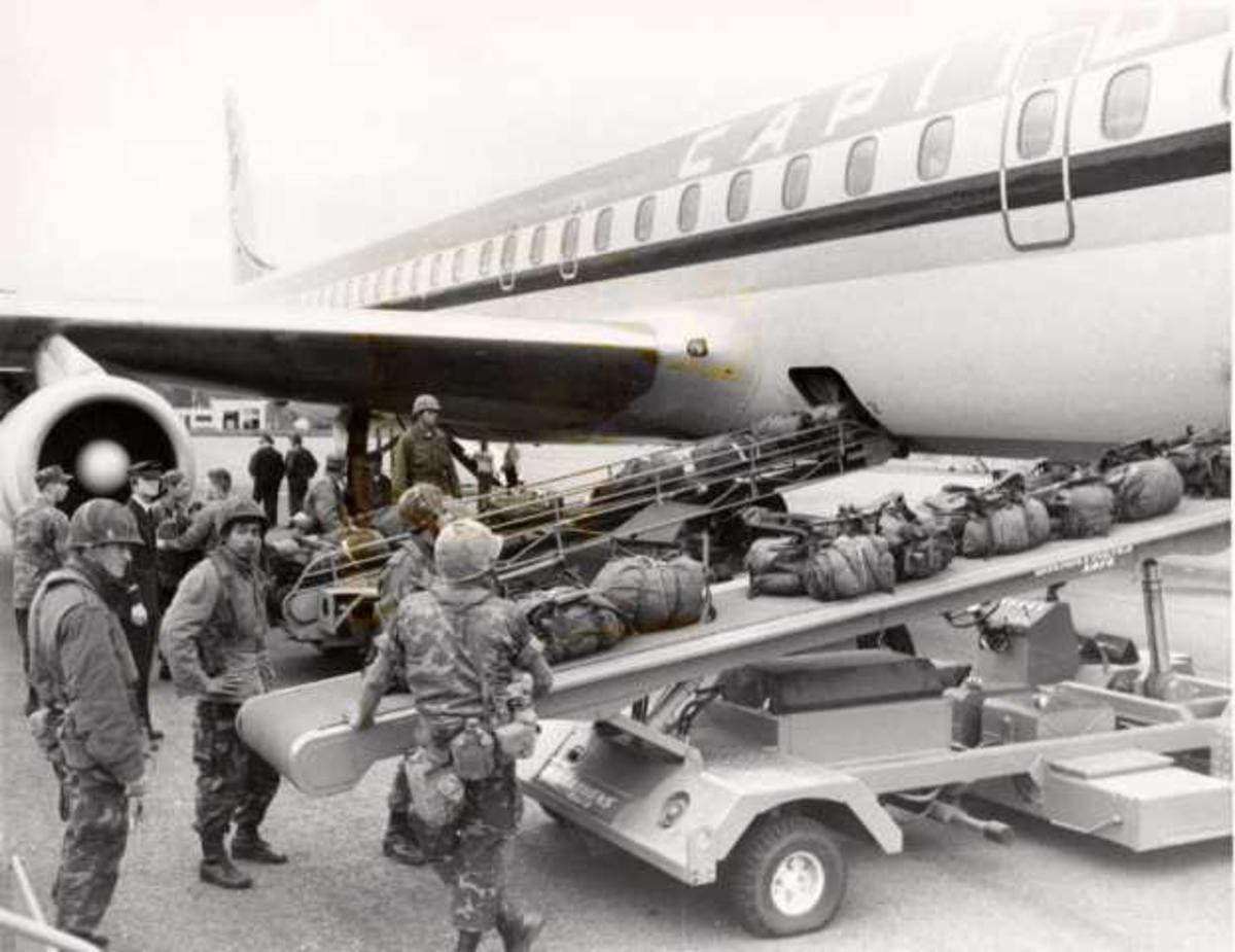 Ett fly på bakken. Douglas DC-8. Flere soldater i forgrunn.