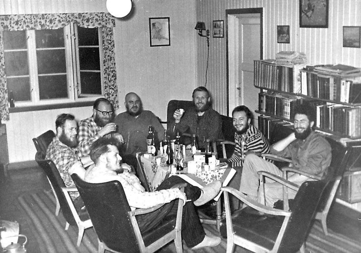 Sju personer som sitter rundt et bord og fester, menn.