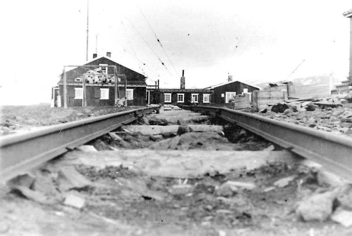 Jernbaneskinner som ligger mot en hus/hytte, værstasjon.