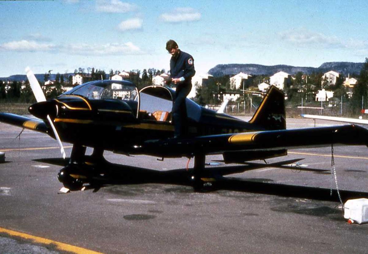 Ett fly på bakken. LN-RAC, Robin R.2160. En person stående på flyets vinge, ved cockpit.