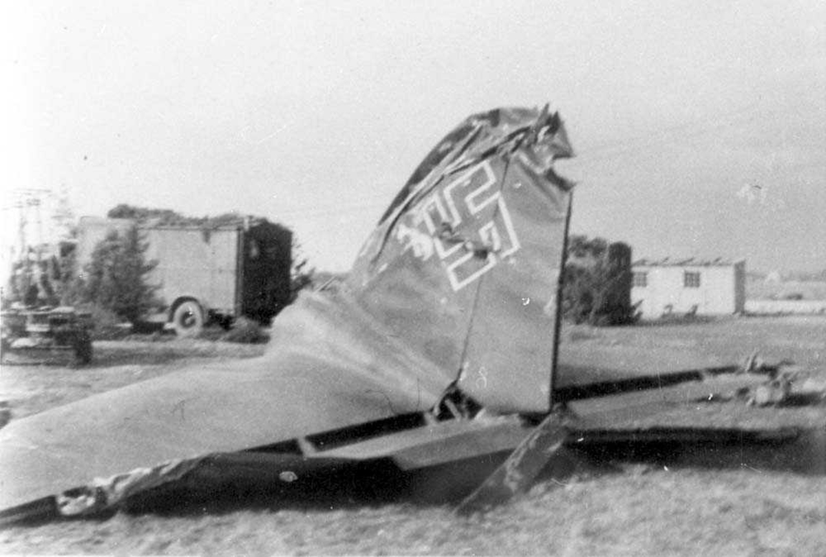 Vrakdeler til et havarert Heinkel He 111, hale og siderorene. Kjøretøy og bygning i bakgrunnen.