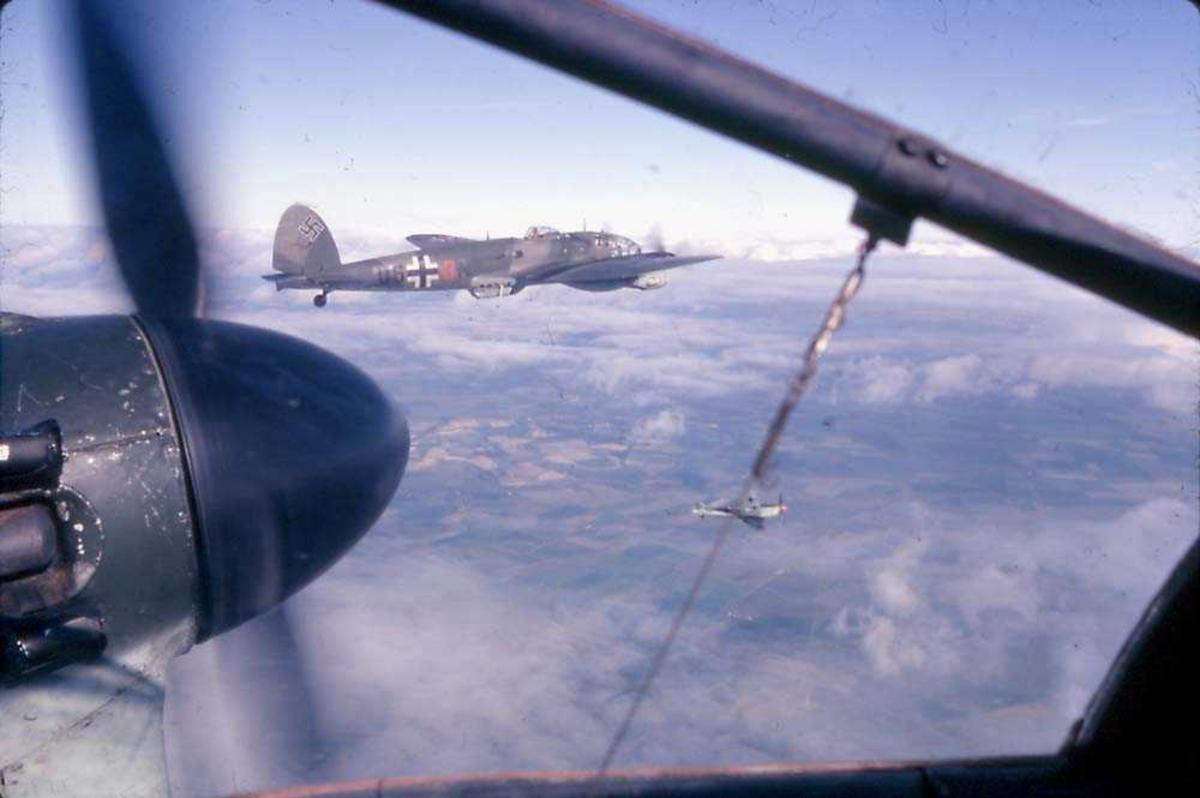 Luftfoto. To fly i luften. Et Heinkel He 111. Bildet er tatt inne i fra annet fly, hvor litt av motoren til flyet sees.