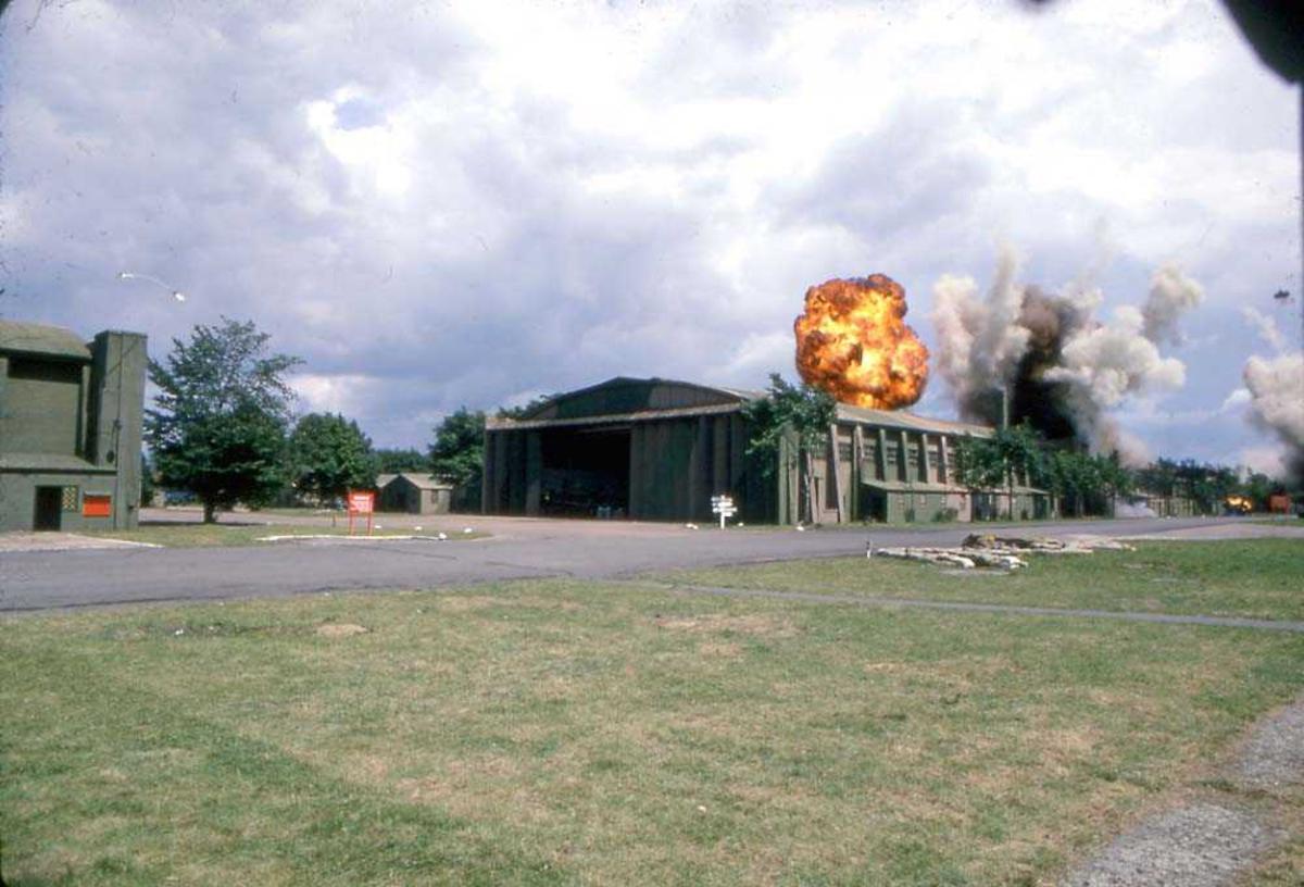 En bygning som blir bombet. Flere bygninger i for og bakgrunnen.