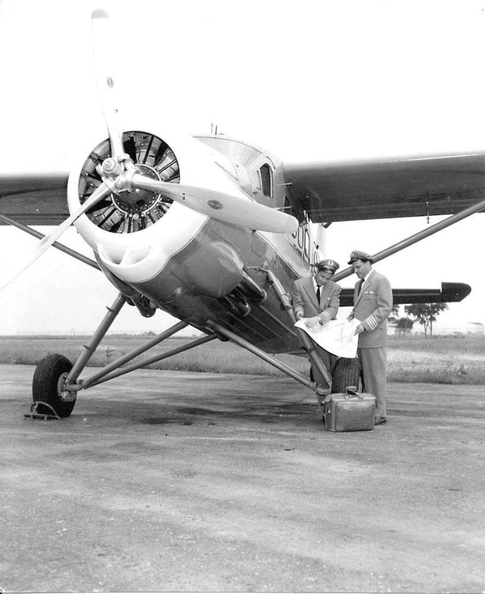 Ett fly på bakken, DHC-3 Otter. To personer i flyveruniform står ved flyet.