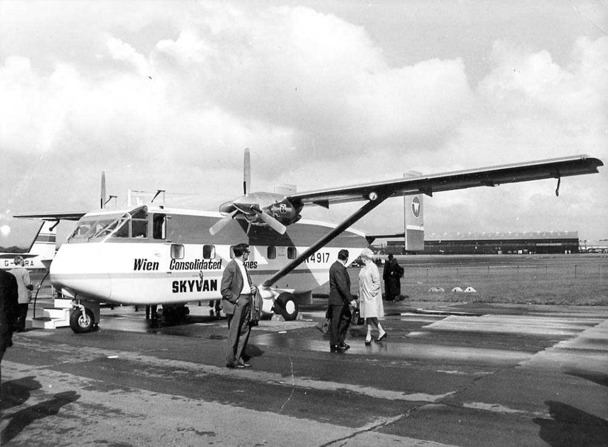 Lufthavn. Ett fly på bakken, Shorts Skyvan Srs 3 N4917 fra Wien Consolidated Airlines. Flere personer ved flyet. Bygning i bakgrunnen.