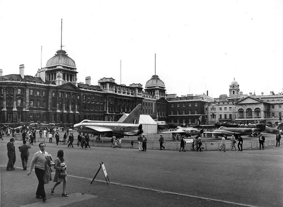 Flyustilling. Flere fly som står utstillt på en åpen plass. Bygninger i bakgrunnen. Flere personer på plassen.