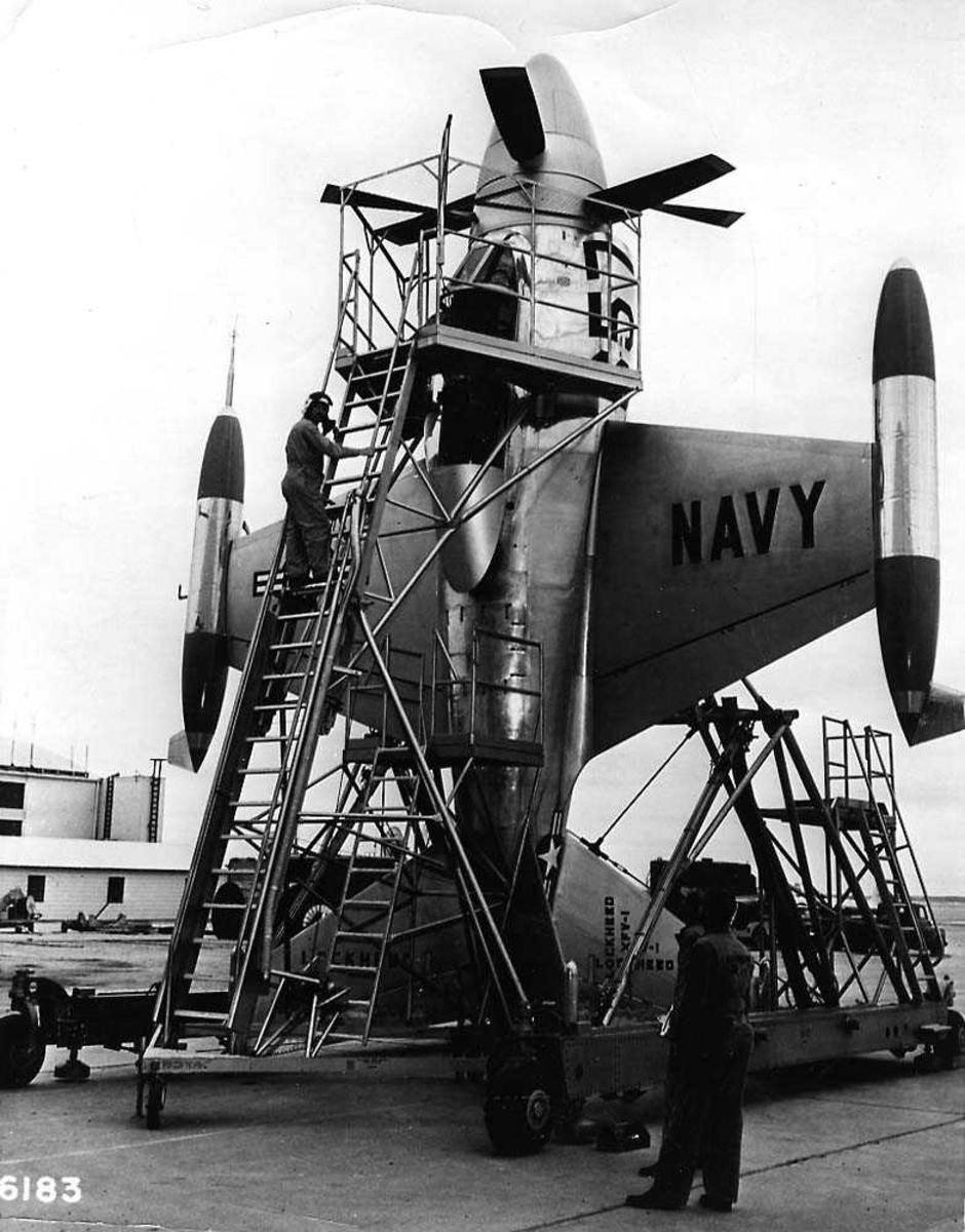 Ett fly på bakken som står vertikalt, Lockheed XFV-1. Et stativ står inntill flyet med en pilot som klatret opp en stige til cockpiten. To personer på bakken.